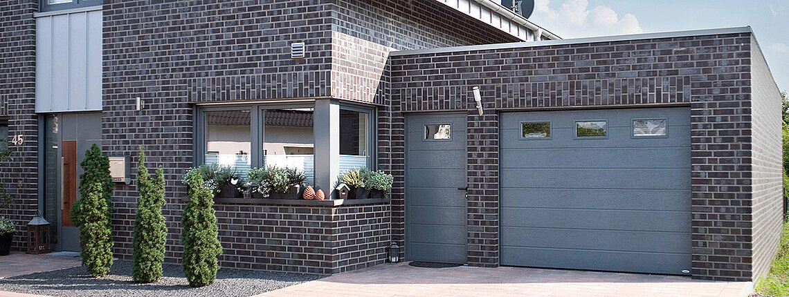 Garagen-Sektionaltor mit ansichtsgleicher Nebentür und Fenster in taubenblau